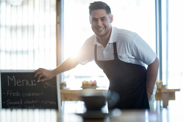 Camarero sonriente escribiendo en el tablero del menú en la cafetería