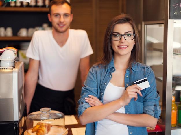 Camarero sonriente y hermosa clienta con tarjeta de crédito