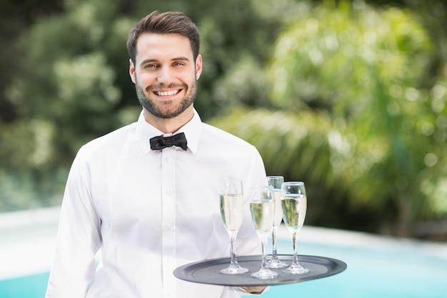 Camarero sonriente llevando flautas de champán en la bandeja