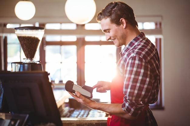 Camarero sonriente con máquina de tarjeta de crédito