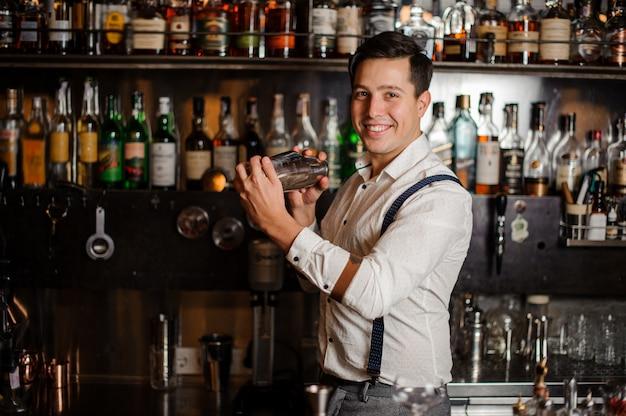 Camarero sonriente está mezclando cóctel
