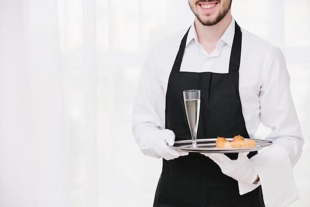 Camarero sonriente presentando bandeja