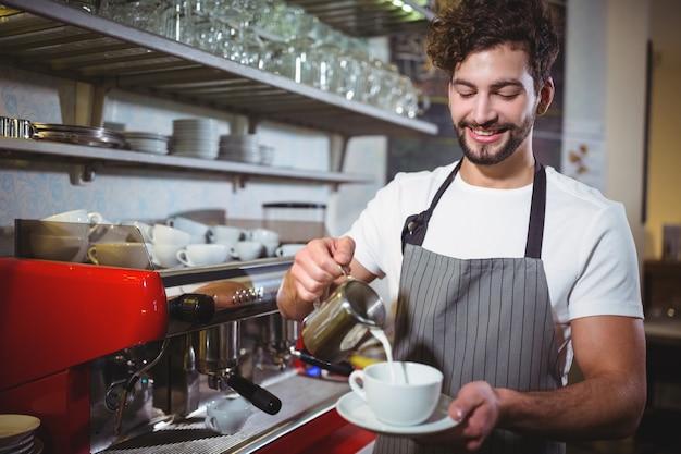 Camarero sonriente que hace taza de café en el mostrador
