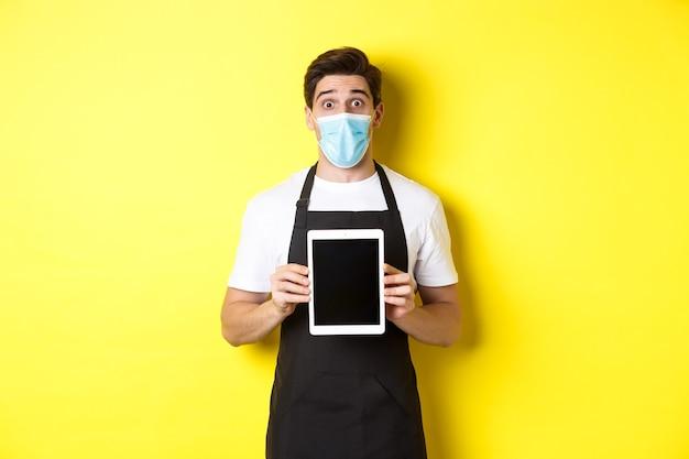 Camarero sorprendido en delantal negro y máscara médica que muestra la pantalla de la tableta, de pie sobre una pared amarilla