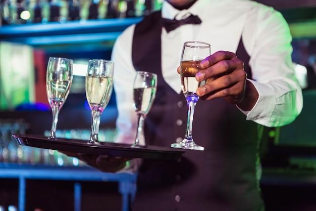 Camarero sosteniendo una bandeja de copas y sirviendo champán en el bar
