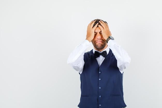Camarero sosteniendo la cabeza con las manos en camisa, chaleco y mirando estresante, vista frontal.