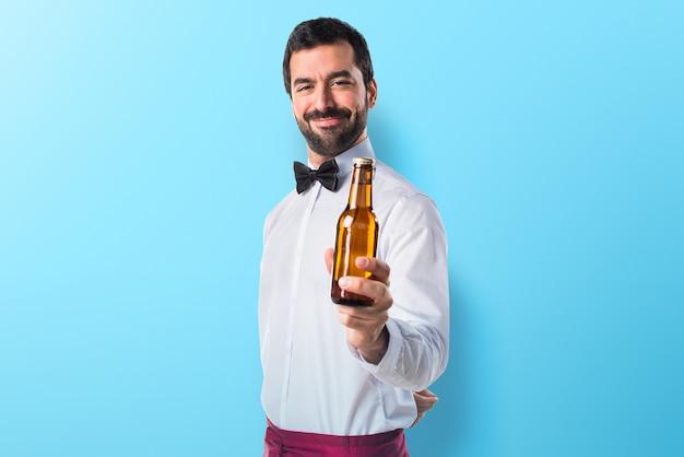 Camarero sosteniendo una cerveza en fondo colorido