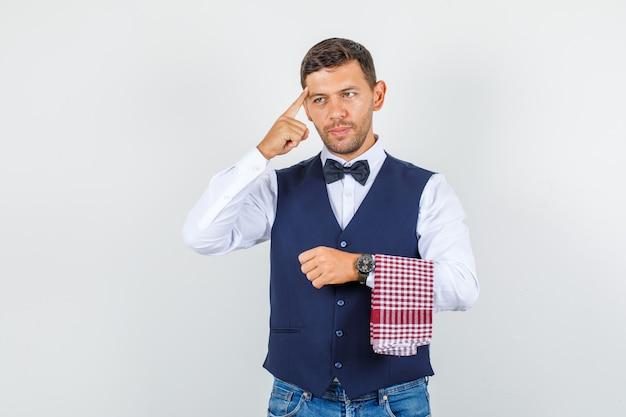 Camarero sosteniendo el dedo en las sienes en camisa, chaleco, jeans, vista frontal.
