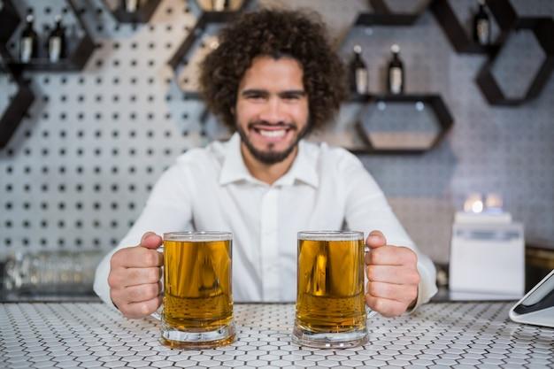 Camarero sosteniendo dos vasos de cerveza en barra de bar