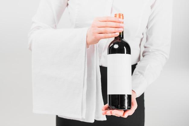 Camarero sosteniendo y ofreciendo botella de vino.