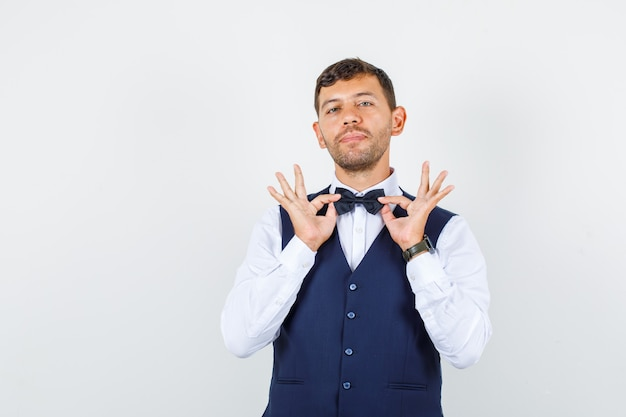 Camarero sosteniendo pajarita en camisa, chaleco y mirando lindo, vista frontal.