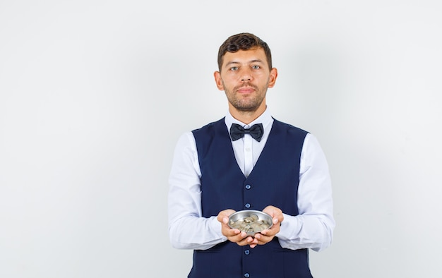 Camarero sosteniendo pila de monedas en camisa, chaleco y mirando confiado, vista frontal.