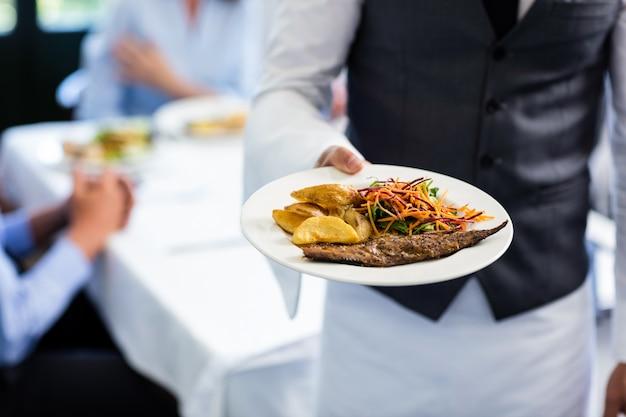Camarero sosteniendo un plato de comida