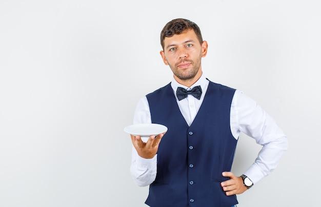 Camarero sosteniendo un plato vacío con la mano en la cintura en camisa, chaleco y mirando suave. vista frontal.