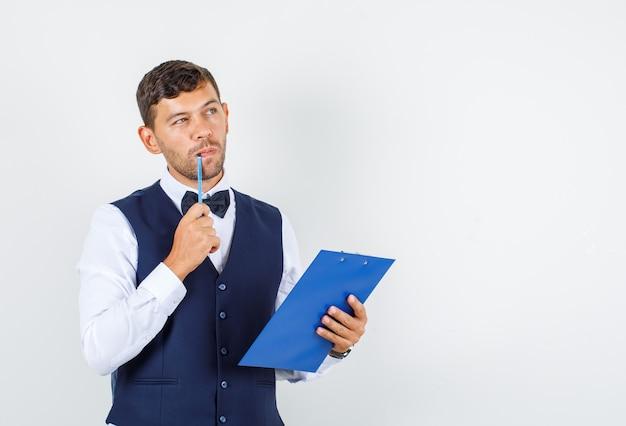 Camarero sosteniendo portapapeles y lápiz en camisa, chaleco y mirando pensativo, vista frontal.