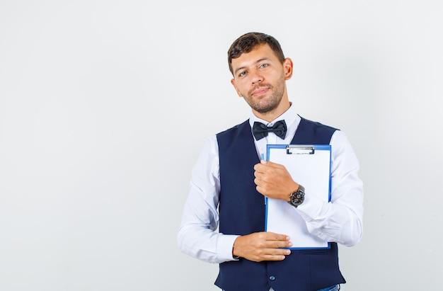 Camarero sosteniendo el portapapeles y sonriendo en camisa, chaleco, vista frontal.