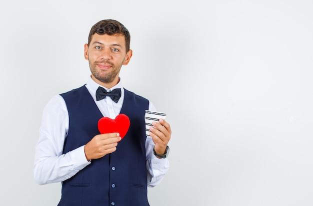 Camarero sosteniendo una taza de bebida y corazón rojo en camisa, chaleco y mirando alegre, vista frontal.