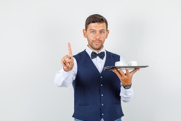 Camarero sosteniendo tazas en bandeja con gesto de espera en camisa, chaleco, pajarita, vista frontal.