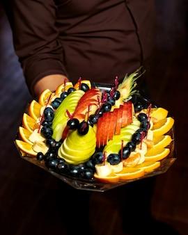 El camarero sostiene un plato de frutas con rodajas de piña, plátano, uva y manzana naranja