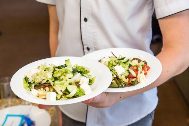 Camarero sujetar dos platos de ensalada, trabajar en evento.