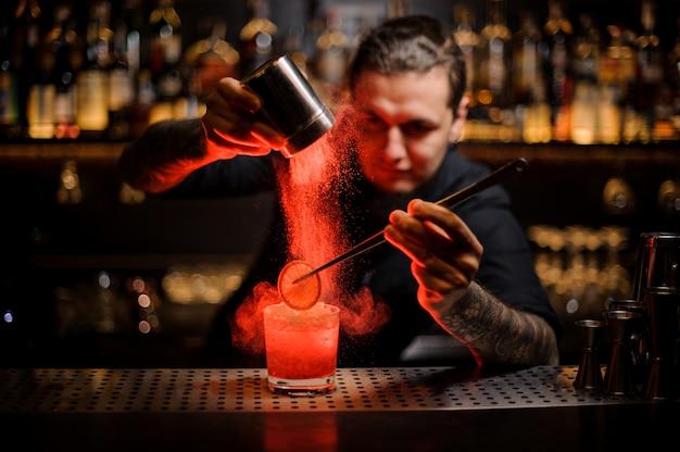 Camarero tatuado agregando especias en polvo en una copa de cóctel con una rodaja de limón