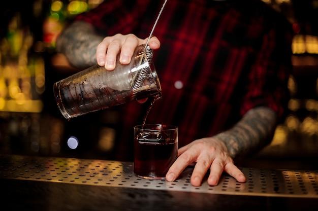 Camarero con tatuajes vertiendo cóctel alcohólico fuerte fresco en un vaso en la barra contra las luces brillantes
