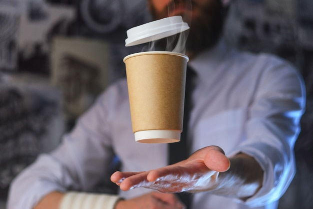 Un camarero y una taza de café caliente