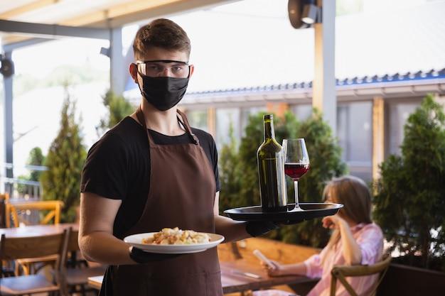 Camarero trabaja en un restaurante con una máscara médica, guantes durante la pandemia de coronavirus