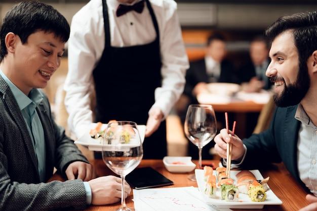Camarero trae sushi a la mesa.