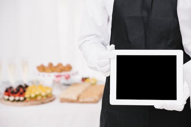 Camarero en uniforme sosteniendo una tableta con maqueta