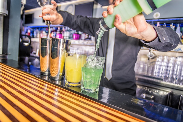 Camarero vertiendo alcohol de la botella y la coctelera