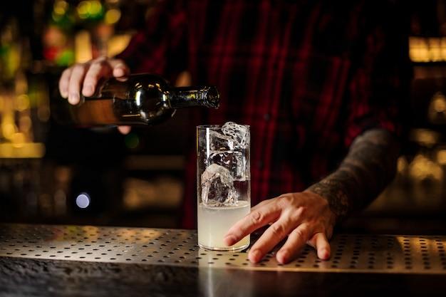 Camarero vertiendo bebida alcohólica de botella en una copa de cóctel con jugo y cubitos de hielo