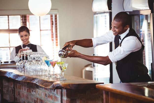 Camarero vertiendo una bebida de una coctelera a un vaso en la barra de bar