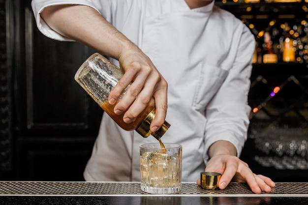 Camarero vertiendo una bebida de una coctelera en un vaso bajo.