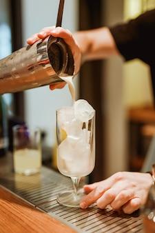 Camarero vertiendo una bebida de piña colada de una coctelera en una copa de cóctel. foto con poca profundidad de campo. imagen de estilo de vida vertical.