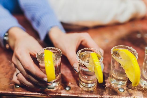 Camarero vertiendo bebidas alcohólicas fuertes en vasos pequeños en la barra, disparos.