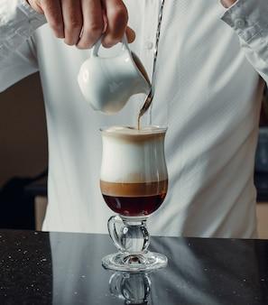 Camarero vertiendo caramelo en la bebida de café de tres colores de la olla de leche