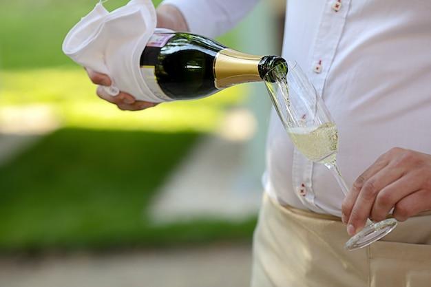 Camarero vertiendo champán en copa con pierna delgada