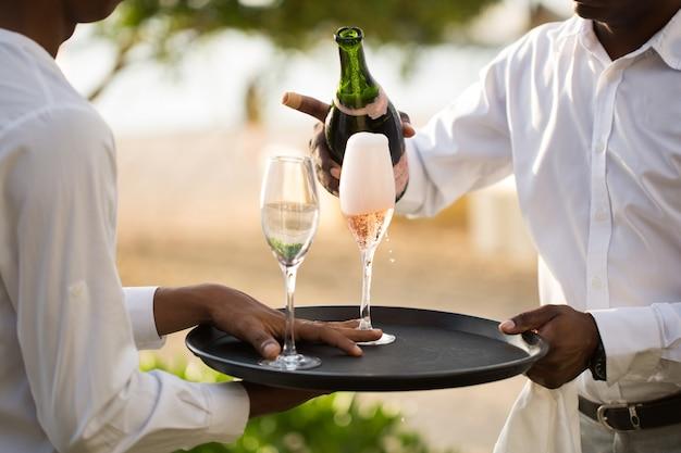 Camarero vertiendo champán en copa.