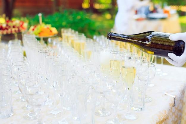 Camarero vertiendo champán en copas