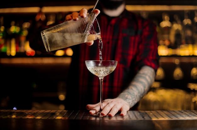 Camarero vertiendo cóctel alcohólico en un vaso elegante en la barra del bar contra las luces