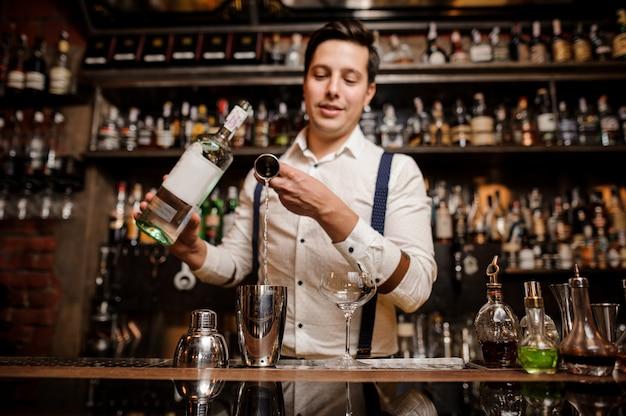 El camarero está vertiendo cóctel fresco en un vaso elegante