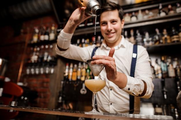 El camarero está vertiendo un cóctel en el vaso y sonriendo