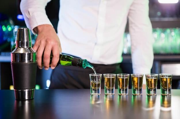 Camarero vertiendo cóctel en vasos de chupito en barra de bar en bar