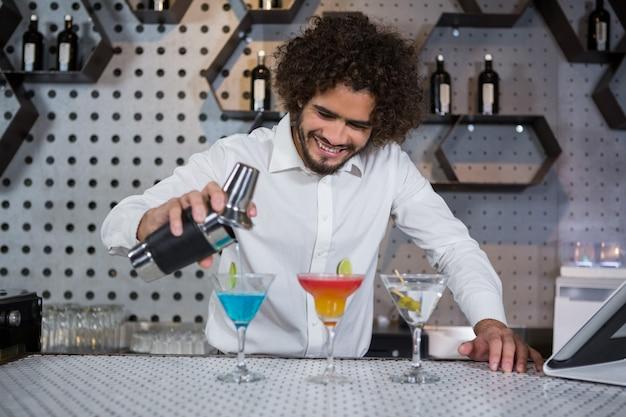 Camarero vertiendo cóctel en vasos