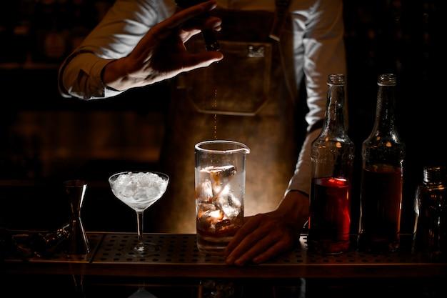 Camarero vertiendo una esencia de la pequeña botella de vidrio