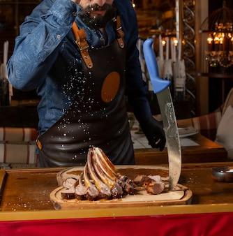 Camarero vertiendo sal sobre costillas de cordero kebab servido sobre tabla de madera