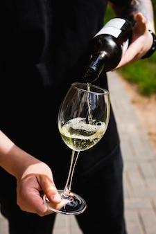Un camarero vertiendo vino blanco en un vaso
