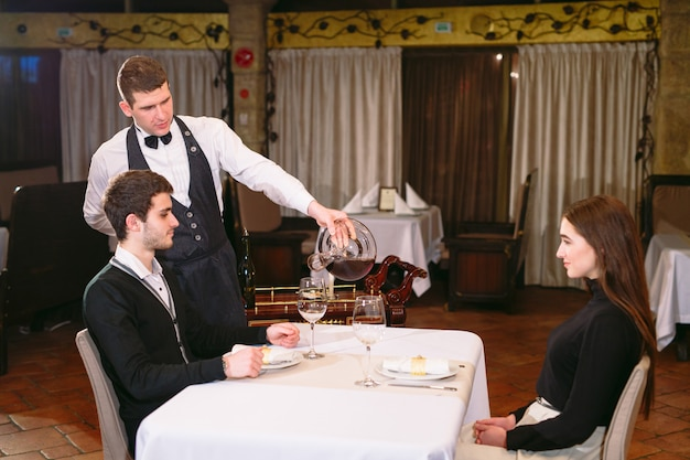 Camarero vertiendo vino tinto en un vaso en una mesa de restaurante