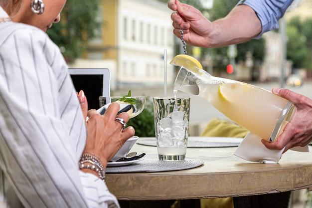 El camarero vierte agua con limón y menta en vasos sobre una mesa para servir.